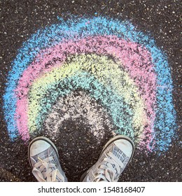 Children's art chalk drawing on Earth: Rainbow painted with colored crayons on asphalt and children's feet in sneakers standing on the asphalt. Top view.