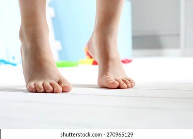 Children's bare feet. Child's bare feet on the wooden floor