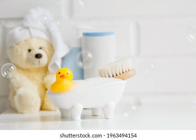 Children's bath accessories. Baby care. Bear with a towel on his head, a brush and bottles of shampoo. A miniature bubble bath and a yellow rubber duckling for bathing.