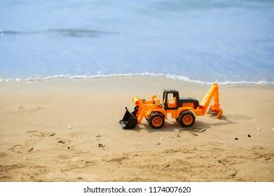 Children's beach toy - excavator on sand on a sunny day