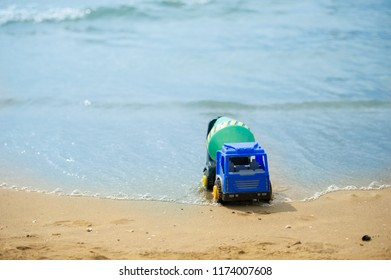 Children's beach toy - plastic truck on sand on a sunny day