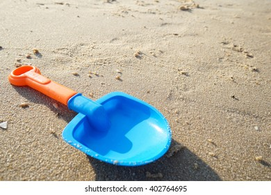 Children's beach toy - spoon toy on sand on a sunny day