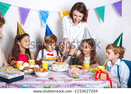 Childrens Birthday Party Kids And Mom Cut Cake