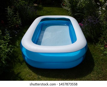 Children's blue and white paddling pool in a small English garden. Landscape and portrait orientation. Background is green planting. Sunny day in summer.