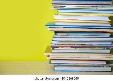 Children's books lie on a bookshelf.