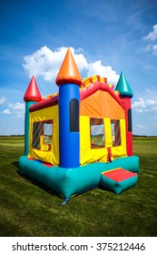 Children's bouncy house castle in a large open yard.