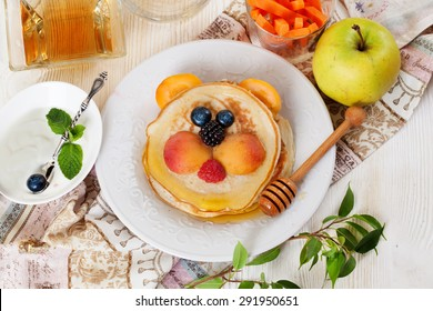Children's breakfast lunch pancakes smiling face of the sun lion strawberry blueberry and apricot, cute food, honey, creative idea dinner kid breakfast  pancake fun breakfast
