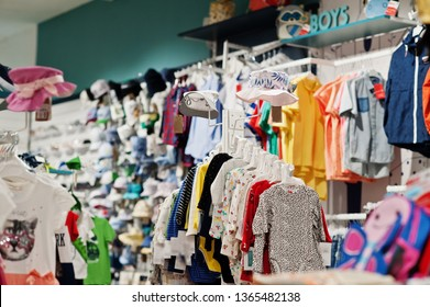 Children's bright clothes hang on the display in the baby clothing store.