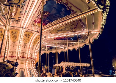 Children's Carousel at an amusement park in the evening and night illumination. amusement park at night. Outdoor vintage colorful carousel in the the city. Vintage photo processing