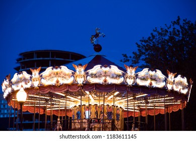 Children's Carousel at an amusement park in the evening and night illumination. amusement park at night. Outdoor vintage colorful carousel in the the city carousel detail. Vintage photo processing