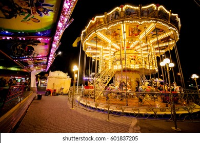 Children's Carousel at an amusement park in the evening and night illumination. amusement park at night. amusement park, picture for the background.
