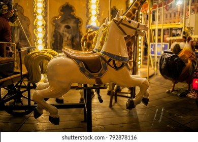 Children's Carousel at an amusement park in the evening and night illumination. amusement park at night. Outdoor vintage retro carousel in the the city. Carousel detail. a toy horse on a carousel