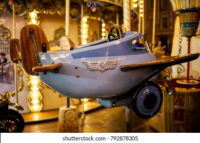 Children's Carousel at an amusement park in the evening and night illumination. amusement park at night. Outdoor vintage retro carousel in the the city. Carousel detail. toy airplane on the carousel