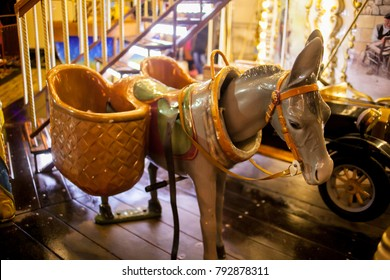 Children's Carousel at an amusement park in the evening and night illumination. amusement park at night. Outdoor vintage retro carousel in the the city. Carousel detail. toy donkey on the carousel