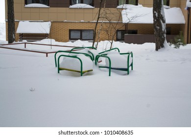 Children's carousel in the snow. In the background the house.Siberia.