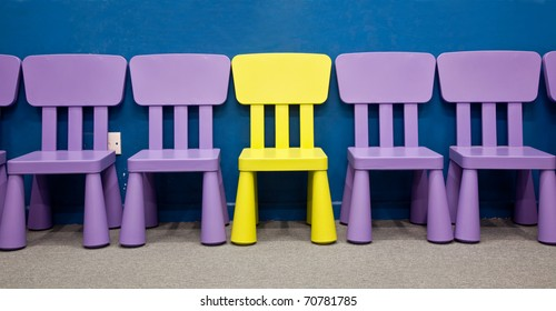 Children's chairs - A yellow colored one in the middle of several purple colored chairs for kids