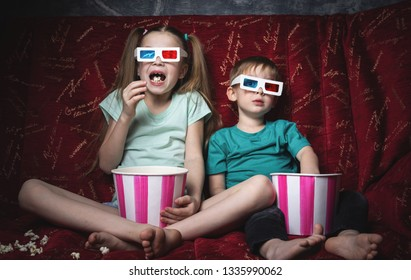 Children's cinema: Children sit on a red sofa and watch a 3D movie.