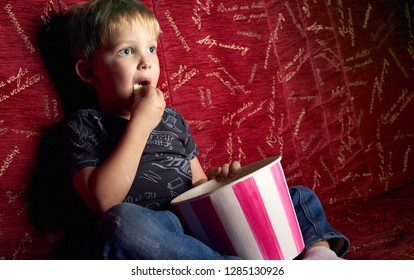 Children's cinema: A little boy is watching a movie in the dark in a red armchair and eating popcorn.