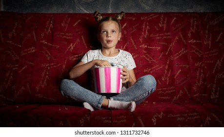 Children's cinema: One schoolgirl girl watches a movie at home on a big red sofa and eats a popkort from a red bucket.