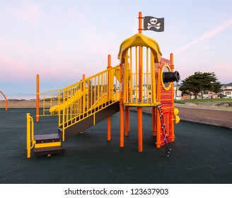 Childrens climbing frame at dawn in shape of a pirate ship with flag