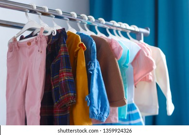 Children's cloth rack, selective focus. Pastel color children's  clothes in a Row on Open Hanger indoors. Clothes for little ladies hung in the children's room. Turquoise and pastel pink colors.