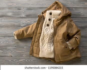 Childrens clothing (knit sweater, hooded canvas jacket). Outfit for little boy. Winter, autumn collection. Fashion, shopping concept. Template for online store, selling. Top view, flat lay