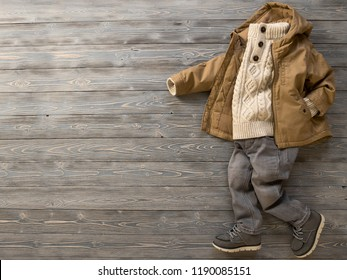 Childrens clothing, shoes (knit sweater, hooded canvas jacket, jeans, suede boots). Outfit for little boy. Winter, autumn collection. Fashion, shopping concept. Template for online store. Flat lay