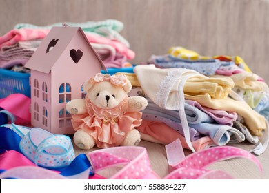 Children's clothing and toys. Pink house and a bear in a dress on a background of clothes for the baby. Sliders and loose jackets stacked in a pile. Bright clothes for children