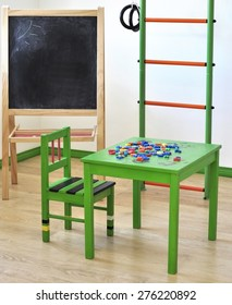 Children's corner in the house. Green table, chair, ladder, chalkboard..Board with space for text