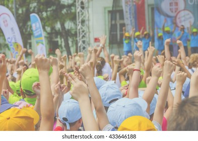 Children's crowd with hands raised at children's summer festival