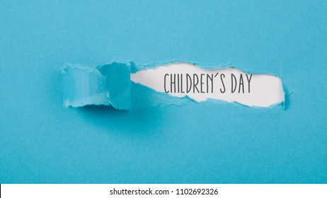 Childrens Day message on torn blue paper revealing secret behind ripped opening.
