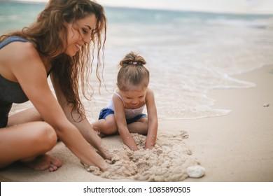 Dia das Crianças. Mamãe e bebê feliz brincando perto da praia. Viajando com sua família, criança. Jogos com criança afetam o desenvolvimento precoce. Importante passar tempo suficiente com seus filhos.
