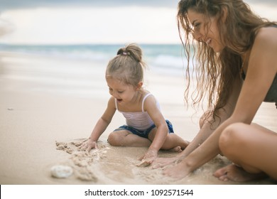 Children's Day. Mom and happy baby playing near the beach. Traveling with your family, child. Games with child affect early development. Important to spend enough time with your kids.