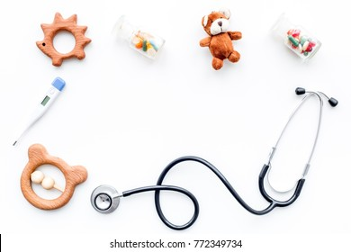 Children's doctor concept. Stethoscope, thermometer, pills, toys on white  background top view copyspace