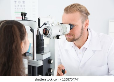 Children's doctor examining little girl with ophthalmic equipment in clinic