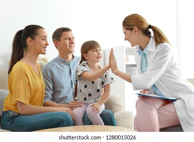 Children's doctor visiting little girl with parents at home. House call