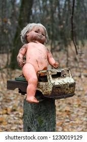 Children's doll and rusty car near abandoned kindergarten in destroyed village of Kopachi (10 km exclusion zone of Chernobyl NPP), Ukraine
