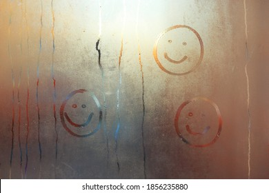 Children's drawing of a smile on the window. A smiling face painted on a fogged window.Draw a face on the fogged glass with your finger