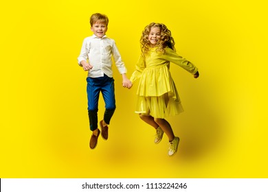 Children's fashion. Beautiful boy and girl in elegant clothes jumping together at studio over yellow background.