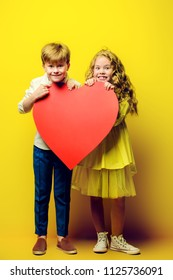 Children's fashion. Beautiful boy and girl in elegant clothes holding big red heart over yellow background. Full length portrait. Valentine's Day.