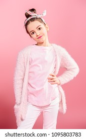 Children's fashion. Cheerful seven year old girl wearing pink cardigan posing over pink background. Studio shot.