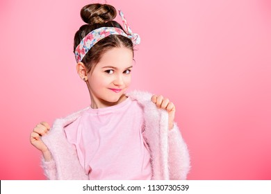 Children's fashion. Cute seven year old girl wearing pink cardigan posing over pink background. Studio shot.