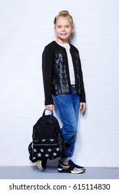 Children's fashion. Modern eight year old girl posing in casual jeans and leather jacket and backpack. Studio shot. Education.