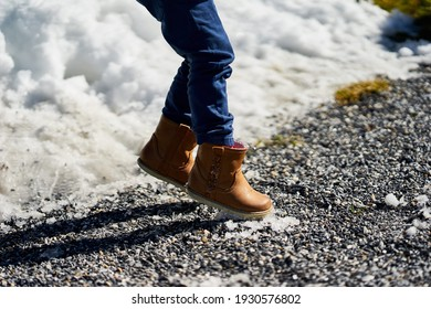 Children's feet in brown boots in jumping with snow in the background