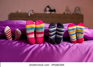 Children's feet in colorful socks. Kid's colorful bright socks. They think they're hidden. Hide and seek.