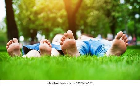 Children's feet  on grass. Family picnic in  park