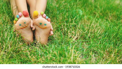 Kinderfüße mit einem Malmuster lächeln auf dem grünen Gras. Selektiver Fokus. Natur.