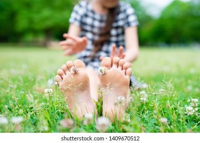 Children's feet sitting in the field