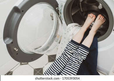 Children's feet in a washing machine with dirty laundry. Purity concept