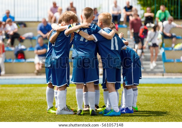 Children's Football Team on the Pitch. Boys in Blue Soccer Kits Standing Together on the Football Field. Motivated Young Soccer Players Before the Final Tournament Game Football Fans in the Background